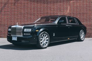 Black Rolls Royce Phantom available for rent in front of red brick wall.