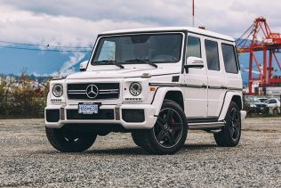 white Mercedes G63 for rent with industrial back drop.