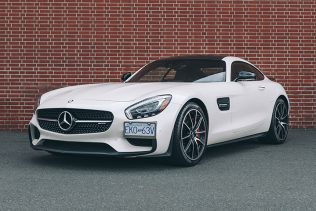 White Mercedes AMG GTS in front of a red brick wall.