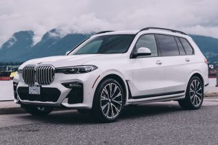 White 2019 BMW X7 rental with mountains and water in the background